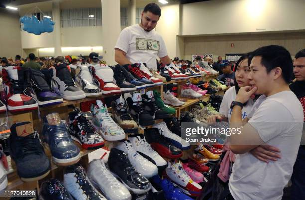 Shoppers inspect sneakers on sale by Texas Shoe Exchange during SneakerCon 2019 at Fort Lauderdale Convention Center on February 2 2019 in Fort...