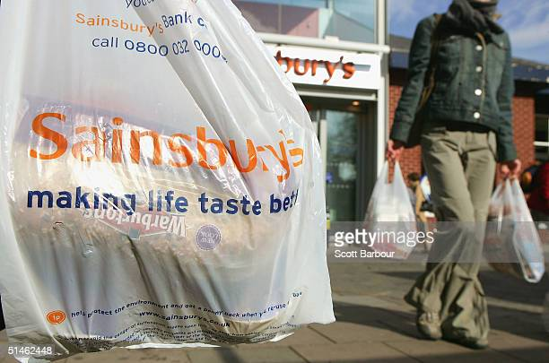 Shoppers leave a Sainsbury's supermarket carrying shopping bags on October 11 2004 in London England Sainsbury's Britain's thirdlargest food retailer...