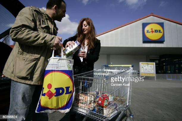 Shoppers leave a supermarket of German discount grocery chain Lidl on March 27 2008 in Berlin Germany Lidl is under investigation by the German...