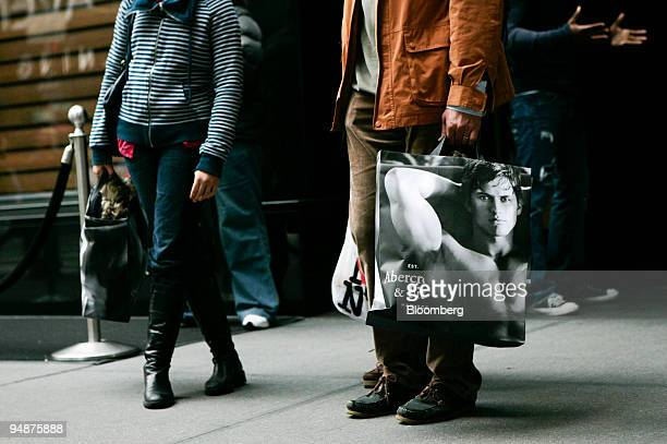 Shoppers leave an Abercrombie Fitch Co store on Fifth Avenue in New York US on Thursday Oct 9 2008 Increasingly reluctant to buy consumers are...