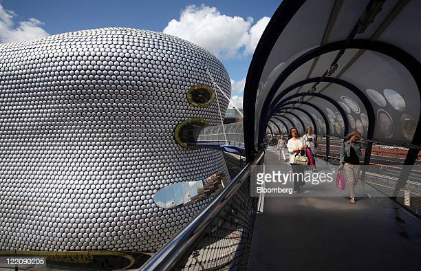 Shoppers leave the Selfridges Co department store by aerial walkway at the Bullring shopping center operated by Hammerson Plc in Birmingham UK on...
