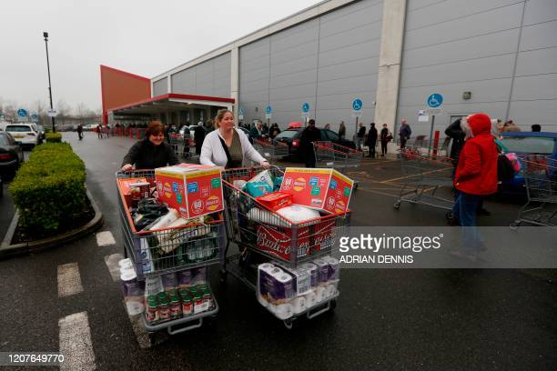 Shoppers leave with baskets piled high with goods at a Costco members wholesale outlet in Farnborough, west of London, on March 19, 2020. - Britain's...