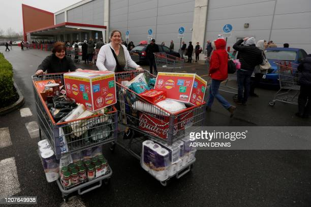 Shoppers leave with trollies piled high with goods at a Costco members wholesale outlet in Farnborough, west of London, on March 19, 2020. -...