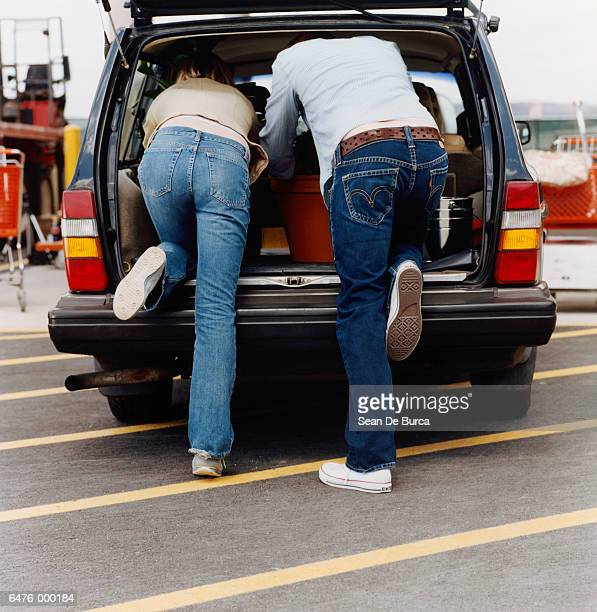 shoppers loading car trunk - bending over stock pictures, royalty-free photos & images