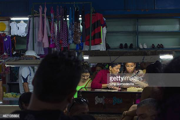 Shoppers look at a small jewelry counter in an indoor marketplace in the Habana Vieja neighborhood January 24 2015 in Havana Cuba After the Cuban...
