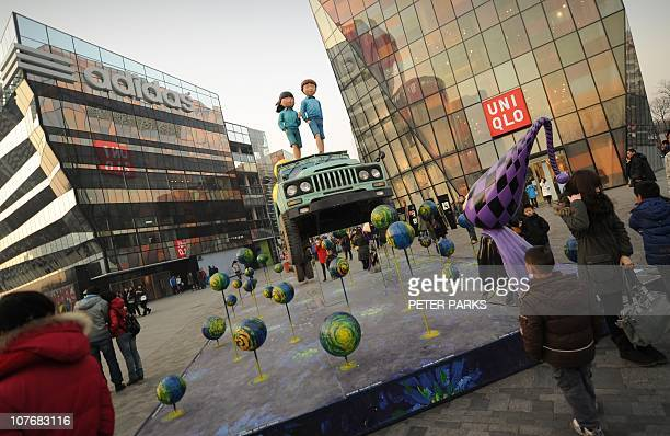 Shoppers look at an art display in The Village shopping mall in Beijing on December 18 2010 China's gross domestic product will exceed 37 trillion...