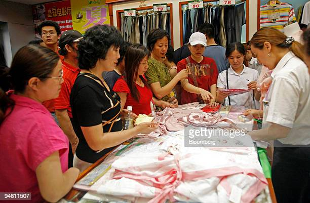 Shoppers look at clothes for sale at a store in Shanghai China Sunday June 11 2006 China's retail sales rose at the fastest pace in 17 months in May...
