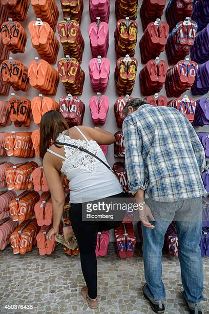 Shoppers look at flip flops at an Alpargatas SA Havaianas store in Sao Paulo Brazil on Saturday June 7 2014 Sao Paulobased Alpargatas SA the maker of...