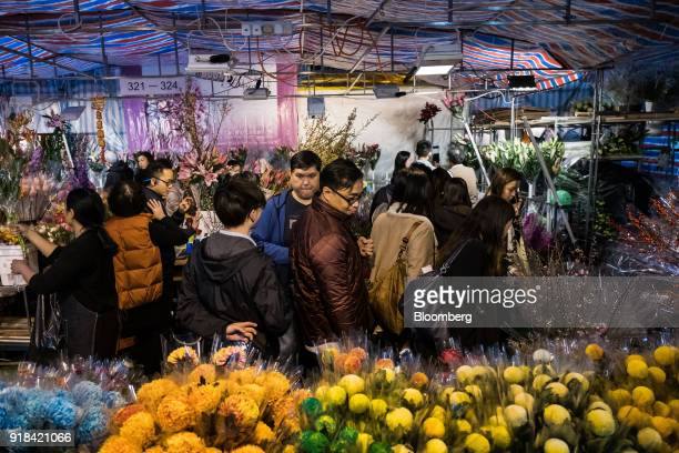 Shoppers look at flowers displayed for sale at the Lunar New Year fair at Victoria Park in Hong Kong China on Wednesday Feb 14 2018 The city's...