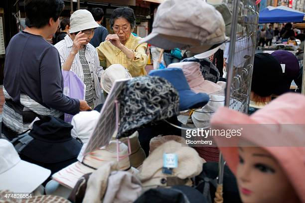 A shoppers look at hats at a stall in a shopping street in the Sugamo district of Tokyo Japan on Sunday May 24 2015 Japan's Topix index fell for the...