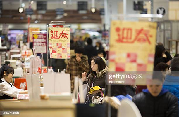 Shoppers look at products displayed on sale at the Aeon Lake Town shopping mall operated by Aeon Retail Co a unit of Aeon Co on the first day of the...