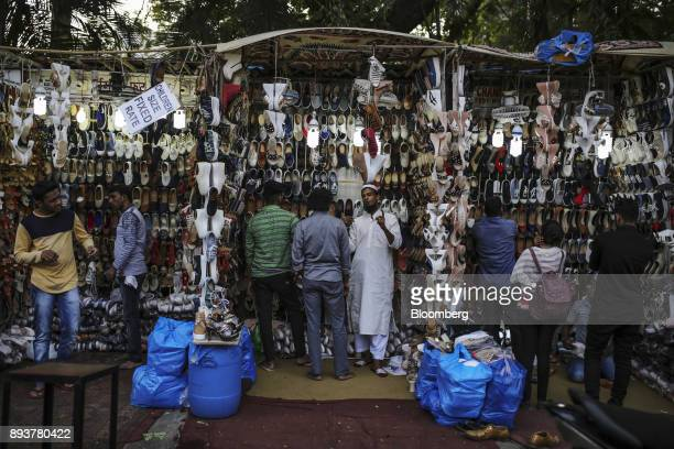 Shoppers look at shoes displayed for sale at a roadside stall in Mumbai India on Friday Dec 15 2017 India's inflation surged past the central bank's...