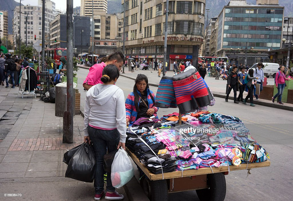 Shoppers look at sox and underwear for sale by a street vendor in Bogota, Colombia, on Wednesday, March 16, 2016. Colombia's central bank raised its benchmark interest rate for a seventh straight month as the inflation outlook continued to worsen and economic growth unexpectedly accelerated. Photographer: Mariana Greif Etchebehere/Bloomberg via Getty Images