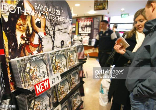 Shoppers look at the new Band Aid 20 music single Do they know it's Christmas on its release in a London music store 29 November 2004 The single is...