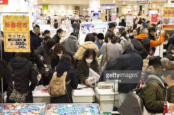 Shoppers look at towels displayed for sale at the Aeon Lake Town shopping mall operated by Aeon Retail Co a unit of Aeon Co on the first day of the...
