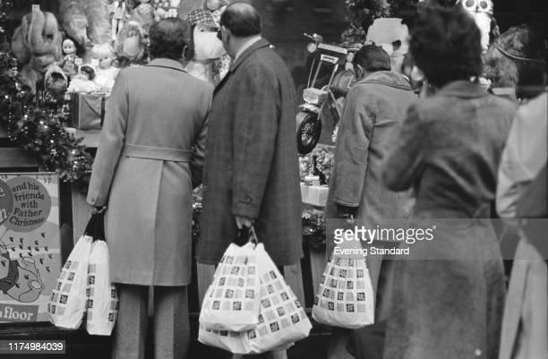 Shoppers looking at a at Marks and Spencer shop window at Christmas time London UK 20th December 1976