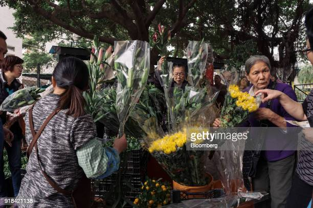 Shoppers looks at bouquets at a flower market ahead of Lunar New Year in the Mong Kok district of Hong Kong China on Wednesday Feb 14 2018 The city's...