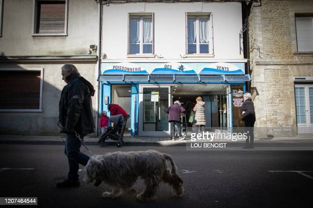 Shoppers maintain distances between each other as they queue outside a fishmongers in Courseulles-sur-Mer, Normandy in northern France on March 17,...