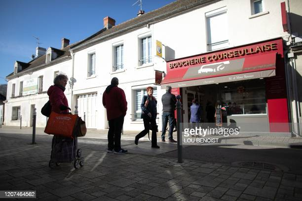 Shoppers maintain distances between each other as they queue outside a butchers shop in Courseulles-sur-Mer, Normandy in northern France on March 17,...