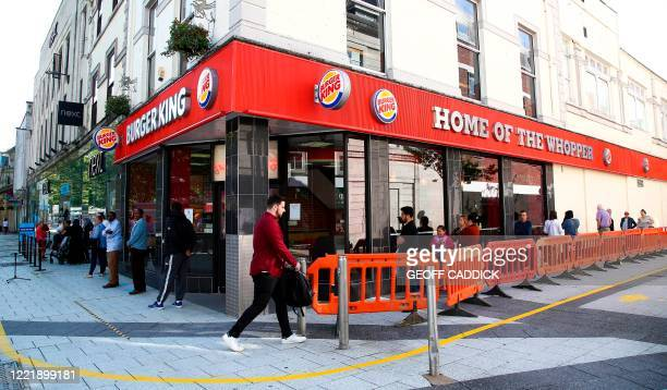 Shoppers maintain the British government's current social distancing guidelines and stand two metres apart as they queue to enter a Burger King fast...