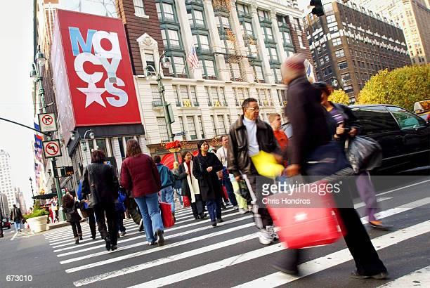 Shoppers make their way across Herald Square near Macy's department store November 23 2001 in New York City The Christmas shopping season started...