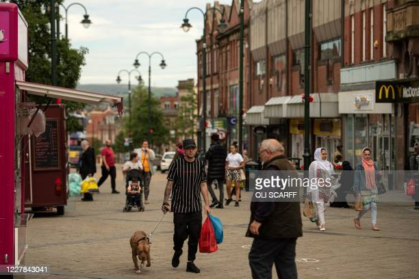 Shoppers make their way through the town centre in Oldham greater Manchester northwest England on July 30 2020