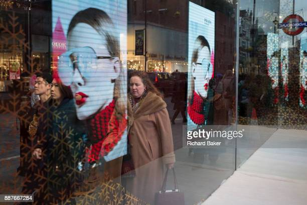 Shoppers merge with the image of a woman's face modelling sunglasses in Covent Garden in central London on 4th December 2017 in London England