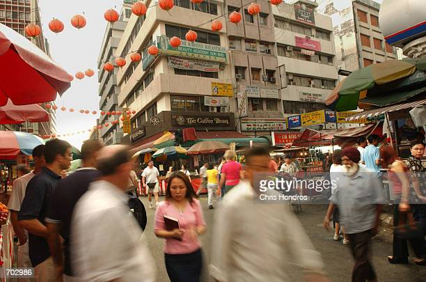 Shoppers mill about Chinatown March 11 2002 in Kuala Lumpur Malaysia Though officially an Islamic country Malaysia is a multiethnic and...