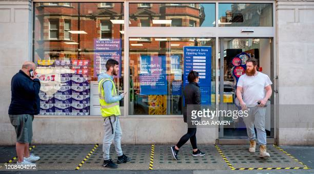 Shoppers observe social distancing as they wait in a queue outside a supermarket in central London on March 27 after Britain's government ordered a...