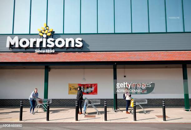 Shoppers observe social distancing as they wait in a queue outside a supermarket in Fleet Hampshire on March 28 2020 The two men leading Britain's...
