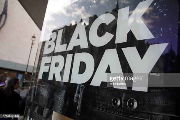 Shoppers on Oxford Street in central London with a sign advertising Black Friday in a shop window on 25th November 2017 in London England United...