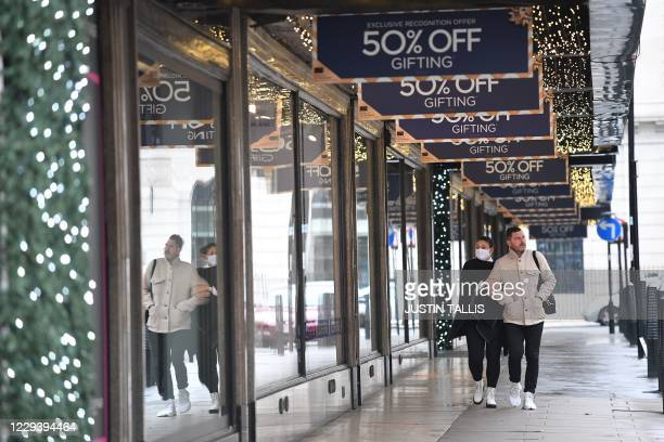 Shoppers, one wearing a mask because of the coronavirus pandemic, walks past a stores advertising sales in London on November 1, 2020 as England...