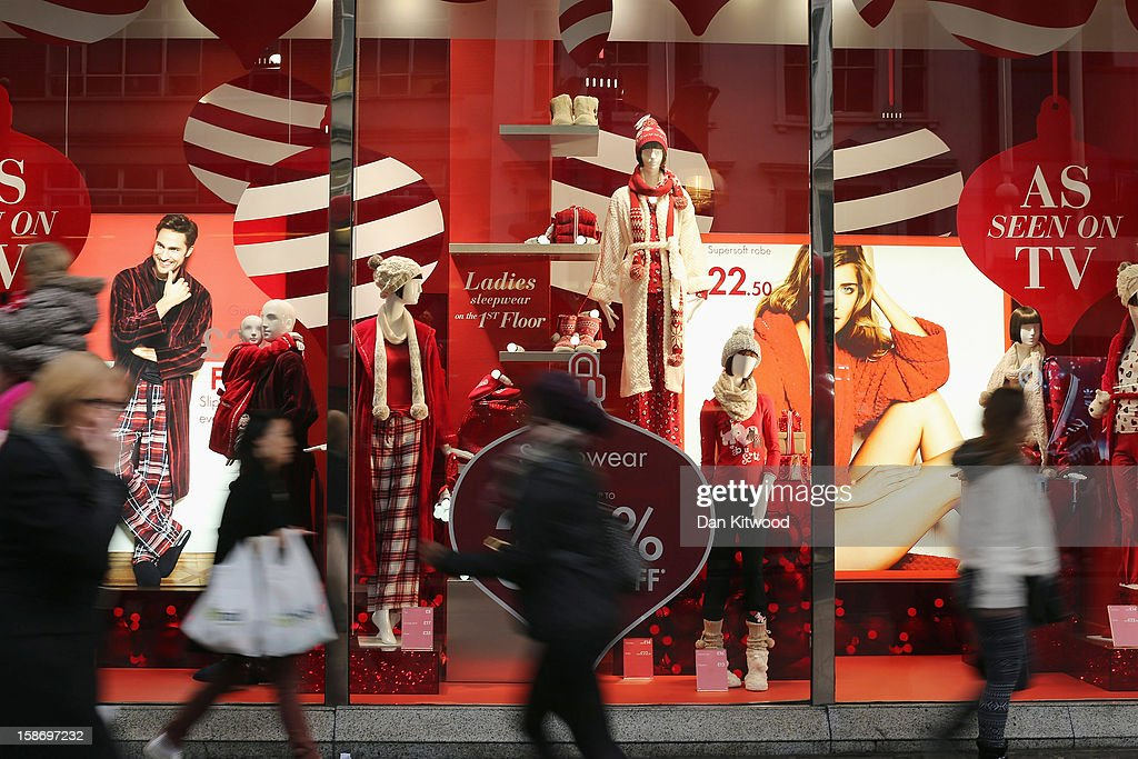 Shoppers pass a clothes shop advertising pre-Christmas sales in Oxford Street on December 24, 2012 in London, England. Many high street retailers have started their sales two days early this year on what is expected to be the busiest shooping day of the year.