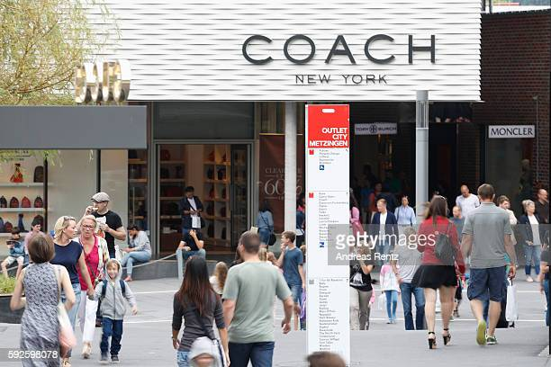 Shoppers pass a Coach store at Outletcity Metzingen on August 19 2016 in Metzingen Germany Metzingen is famous for its factory outlets attracting...