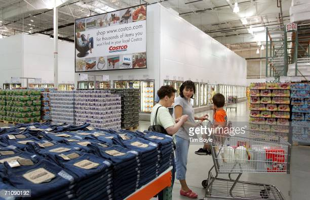Shoppers pass a display of jeans in a Costco Wholesale store May 31 2006 in Mount Prospect Illinois Thirdquarter earnings reported today were up at...
