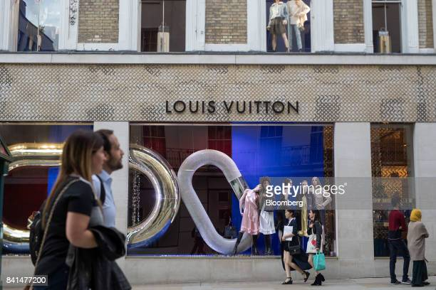 Shoppers pass a display of luxury fashion apparel in the window of a LVMH Moet Hennessy Louis Vuitton SE store on New Bond Street in central London...
