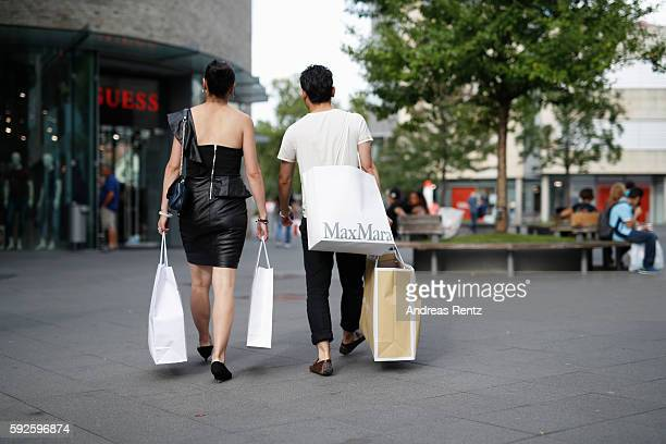Shoppers pass a Guess store at Outletcity Metzingen on August 19 2016 in Metzingen Germany Metzingen is famous for its factory outlets attracting...