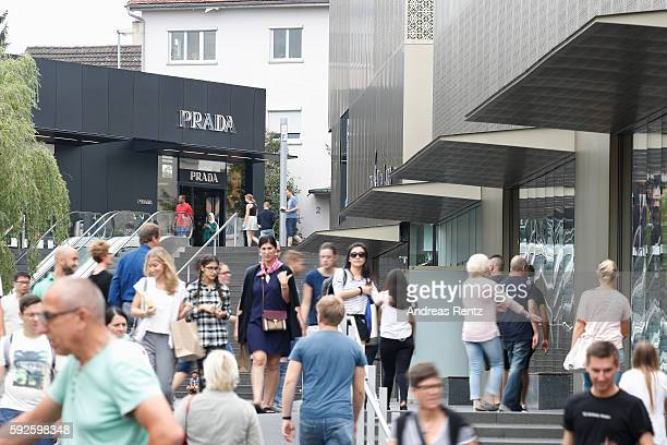 Shoppers pass a Prada store at Outletcity Metzingen on August 19 2016 in Metzingen Germany Metzingen is famous for its factory outlets attracting...