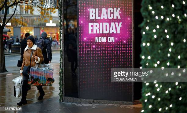 Shoppers pass a promotional sign for 'Black Friday' sales discounts outside a store on Oxford Street in London on November 26 2019 Black Friday is a...