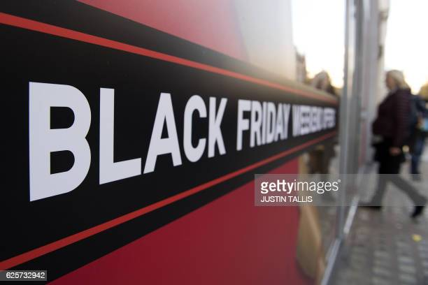 Shoppers pass a promotional sign for 'Black Friday' sales discounts as they enter a retail store on Oxford Street in London on November 25 2016 Black...