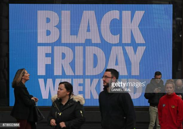 Shoppers pass a promotional sign for 'Black Friday' sales discounts on Piccadilly Circus in London on November 24 2017 Black Friday is a sales offer...