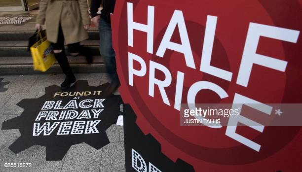 Shoppers pass a retail store's 'Black Friday' advertisement as they exit a shop on Oxford Street in central London on November 24 ahead of the annual...