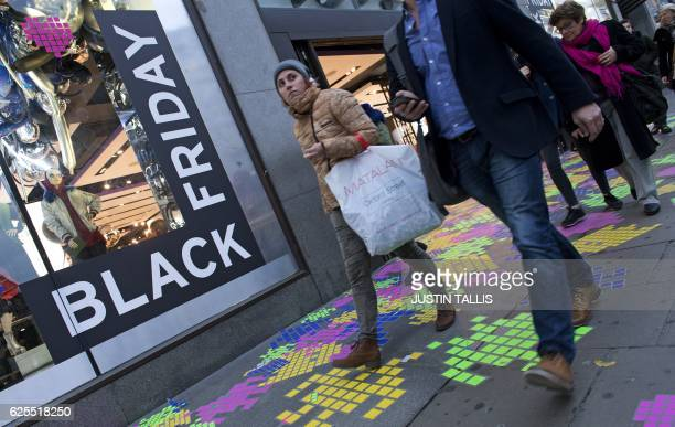 Shoppers pass a retail store's 'Black Friday' advertisement on Oxford Street in central London on November 24 ahead of the annual retail event...