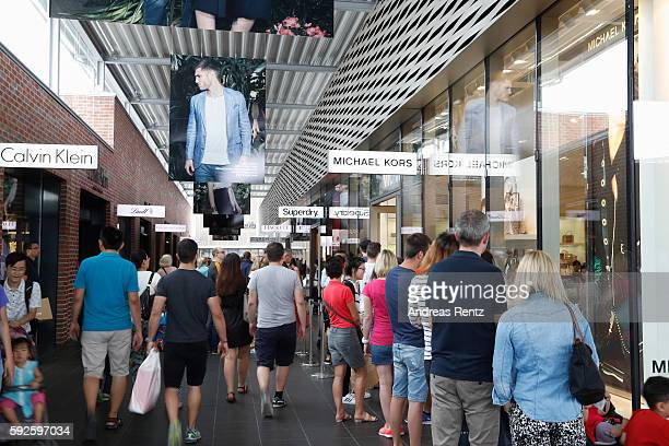 Shoppers pass a shopping arcade at Outletcity Metzingen on August 19 2016 in Metzingen Germany Metzingen is famous for its factory outlets attracting...