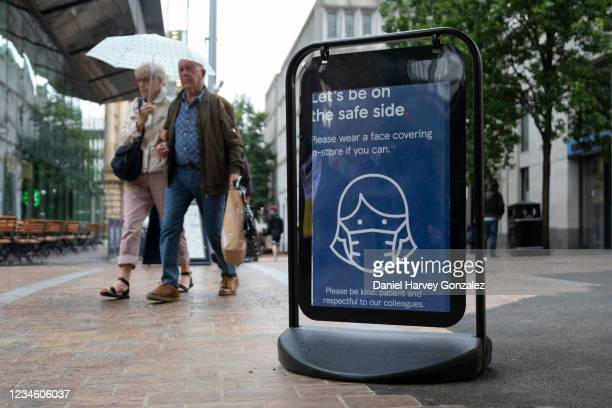 Shoppers pass a sign outside a Tesco, one of Britain's largest and most popular supermarkets, asking that members of the public wear masks to reduce...