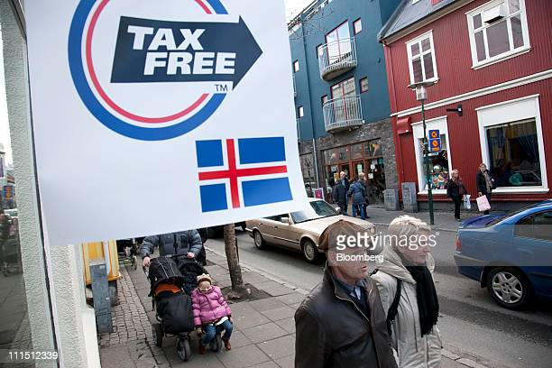 """Shoppers pass a sign reading """"tax free"""" which hangs outside a store in Reykjavik, Iceland, on Saturday, April 2, 2011. Icelandic voter support for a..."""