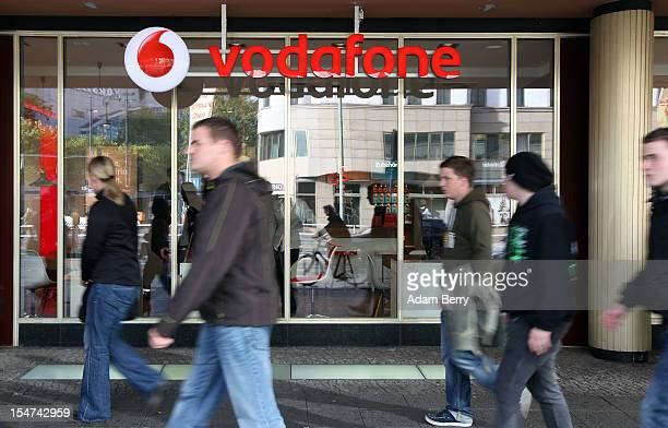 Shoppers pass a Vodafone shop on October 25, 2012 in Berlin, Germany. Retail business is the third-biggest economic sector in Germany, and consumer...