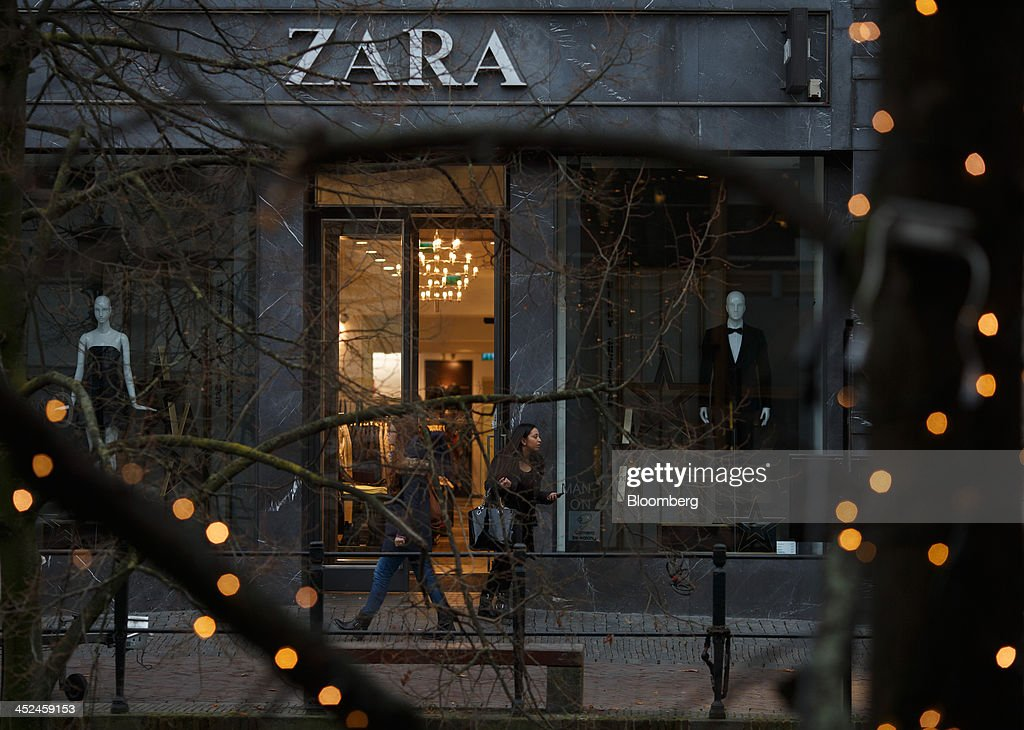 Shoppers pass a Zara fashion store, operated by Inditex SA, in Utrecht, Netherlands, on Friday, Nov. 29, 2013. European government bonds were little changed as investors showed a muted reaction to Standard & Poor's decision to raise its outlook on Spain's debt and strip the Netherlands of its top credit rating. Photographer: Jasper Juinen/Bloomberg via Getty Images