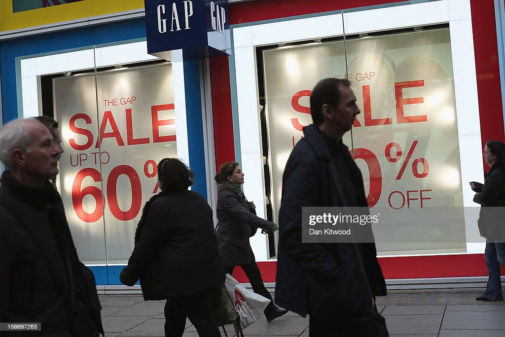 Shoppers pass aclothes shop advertising pre-Christmas sales on Oxford Street on December 24, 2012 in London, England. Many high street retailers have started their sales two days early this year on what is expected to be the busiest shooping day of the year.