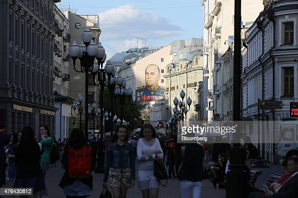 Shoppers pass beneath a wall mural depicting Russian General Georgy Zhukov a World War II Soviet hero on Arbat street in Moscow Russia on Monday June...
